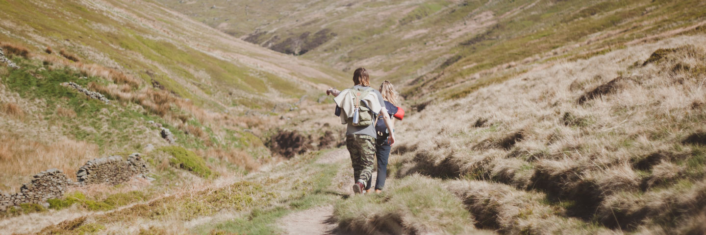 2 people walking in the grassy hills